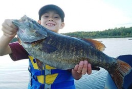 Young boy holds a monster summer smallmouth.
