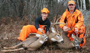 'Quick, hide Ken's rifle,' someone in camp whispered, while this photo was being taken. Pictured (left to right) are Doc's grandson, Ryan, Doc's youngest son, Ken, and the three bucks taken by Ken Nordberg three seasons ago. All were taken from stand sites near very fresh buck tracks.