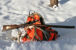 Wood stock Hawken muzzleloader rifle with deer antlers on orange hunting pack in the snow.