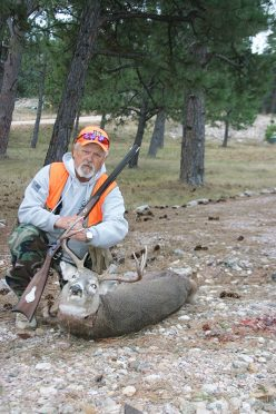 Hunter L.P. Brezny with a downed whitetail deer and the Hawken muzzleloader rifle.