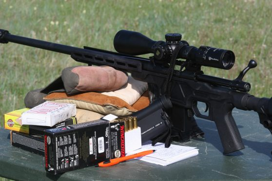 Black finish Howa chassis rifle with open bolt and scope, resting on shooting bags with open box of Winchester .308 ammunition nearby and shooters log notepad.