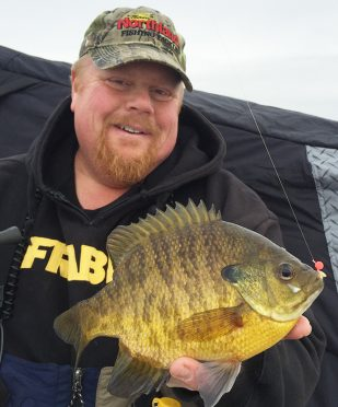 Brian Brosdahl holding a plate-size bluegill caught while ice fishing.