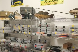 Well organized shelves with stacks of Plano tackle box inserts on wire racks. Off-season prep gets things ready for spring success!