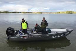 Three men--Brandon Schreiber, John Cleveland, and Mike McGuire--in an 18-foot Crestliner Kodiak boat on Cree Lake in Saskatchewan.