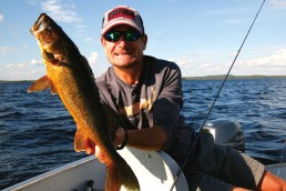 Fisherman in sunglasses--Roger Cormier--holds up a sizable golden walleye just caught from Wabakimi Lake on his recent fishing adventure.