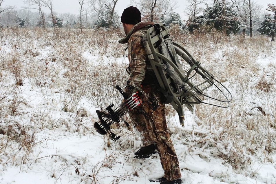 Late-season archery expert Tim Kjellesvik heading to his deer hunting location through a snowy field.
