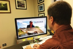 Man at computer monitor researching fishing destinations for his trip of a lifetime.