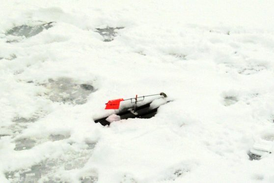 A tip-up on the ice for indicating fish activity.