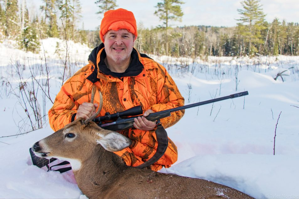 "Deer hunter in the snow with small ""spike buck"" deer and rifle."