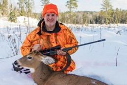 Deer hunter in the snow with small