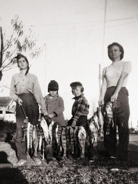 Black and white photo of two women and two children--one is Rick Clunn--holding a stringer of fish.