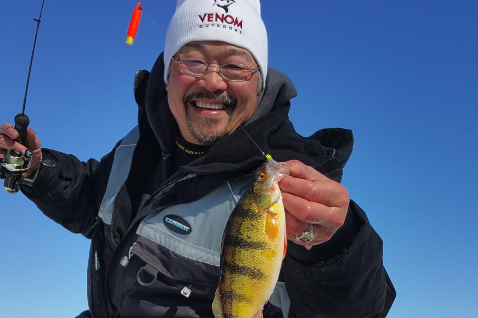 Ted Takasaki, professional walleye angler and author, displays a freshly caught fish found lurking under the ice.