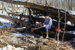 Young man in survival shelter lean-to in winter.