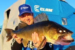 Ice angler and guide captain Chris Granrud holds up a trophy golden walleye caught while ice fishing.