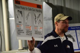 Man holding a poster with the three basic rules of safe gun handling at a concealed carry course.