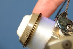 Fishing reel and index finger.