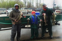 Peter Olson poses with friend Kasey Krueger and dad Geremy Olson in front of fishing boat in a parking lot.