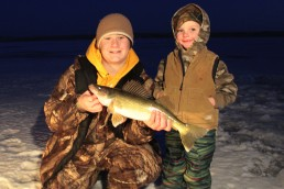 Two ice-fishing young anglers with a fresh catch.
